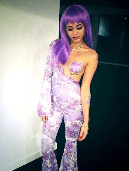 """IMITATION IS THE SINCEREST FORM OF FLATTERY! MILEY CYRUS CHANNELED YET ANOTHER SINGER AS SHE DRESSED AS LIL' KIM, CIRCA THE 1999 MTV VIDEO MUSIC AWARDS. THE """"WE CAN'T STOP"""" SINGER SHARED A SELFIE OF THE PURPLE AND VERY REVEALING OUTFIT WITH HER FANS VIA TWITTER."""
