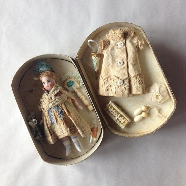 Antique French all-bisque doll with accessories and extra dress in antique box.
