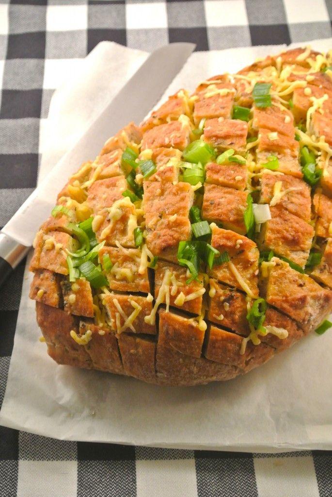 Gevuld snackbrood met bosui (ingrediënten: heel brood (ongesneden), roomboter, knoflookpoeder, peterselie, basilicum, chilipoeder, bosui en kaas) (@ Lekker & Simpel)