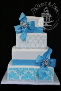 A blue and white wedding cake covered with fondant and decorated with Damask stenciling, quilting, blue fondant bows, and a little sparkle! www.phdserts.com