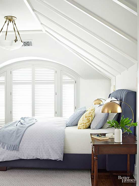 A squared-off peak, arched window, and beam detailing give the master bedroom cozy appeal. Painting woodwork and walls all white and adding dollops of soft blues create a retreat that's calming for the end of the day.