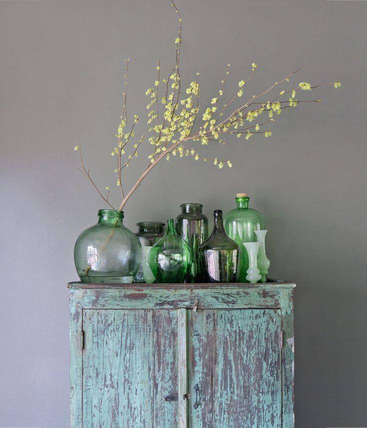 Flessen en vazen in dezelfde kleurschakeringen in verschillende maten en vormen bij elkaar maakt een mooi stilleven.
