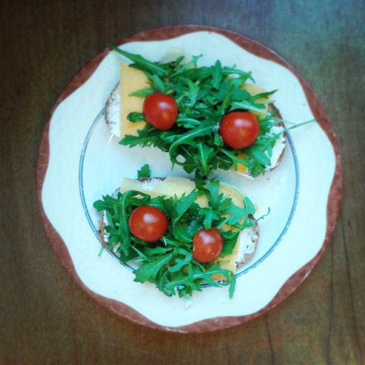 Snídaně: celozrnný chléb, Lučina, cheddar, rukola a rajče.