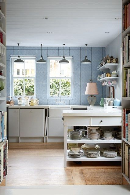 Blue kitchen wall tiles with white units & island. Hanging pendant lights & vintage accessories in Rita Konigs home. Kitchen design ideas from House & Garden; worktops, tiles, cabinets & sinks.