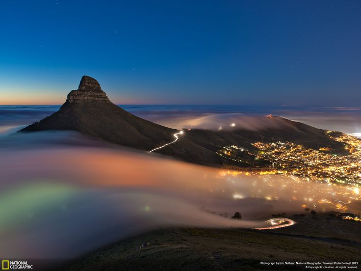 Taken one evening in April 2013 this long-exposure image shows a bank of fog rolling off the Atlantic Ocean, over Kloof Nek & Signal Hill and into the city of Cape Town | Photo captured by Eric Nathan