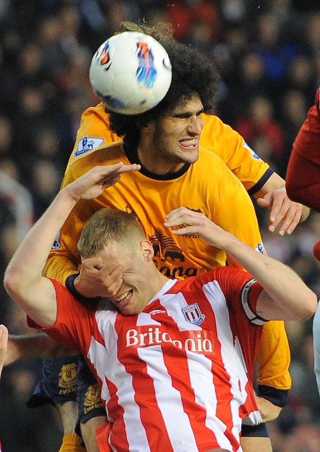 Everton's Belgian midfielder Marouane Fellaini (top) vies for the ball with Stoke City's English defender Ryan Shawcross during a English Premier League match. (AFP Photo)