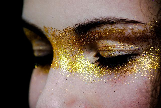 dramatic face make-up. Gold flake, glitter across eyes & nose. Mask, runway, photoshoot.