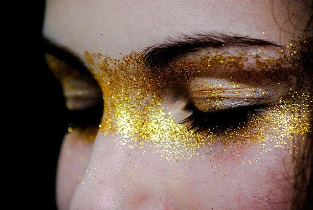 dramatic face make-up. Gold flake, glitter across eyes & nose. Mask, runway, photoshoot.