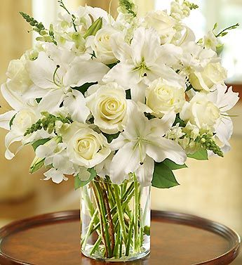Glorious roses lead the way in this luxurious white arrangement. Paired with lilies, snapdragons and salal, they're hand-gathered in a stylish cylinder vase to evoke an evening stroll.