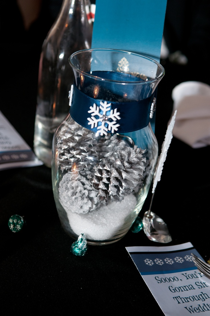 "Wedding centerpiece. Vase, epsom salt for snow, silver spray painted pinecones, sprayed with spray adhesive to make the ""snow"" stick to the pinecones when I poured it in the vase. Complete with a ribbon and snowflake"