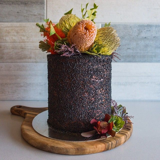 A woodland-inspired wedding cake for my collaboration with @prettypedestals, showcased at Sydney's @onefinedayweddingfairs! This guy is a red velvet & chocolate brownie layer cake, filled with Nutella cream cheesecake, covered with black sesame seeds & adorned with some of my favourite Australian native plants & flowers.