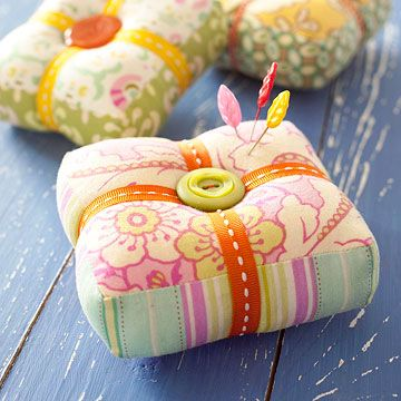 Patchwork Pincushion  Bold fabric, zany buttons, and quirky ribbons elevate the practical pincushion to new heights of style.  Designed by Heather Bailey  http://www.bhg.com/crafts/sewing/accessories/patchwork-pincushion/
