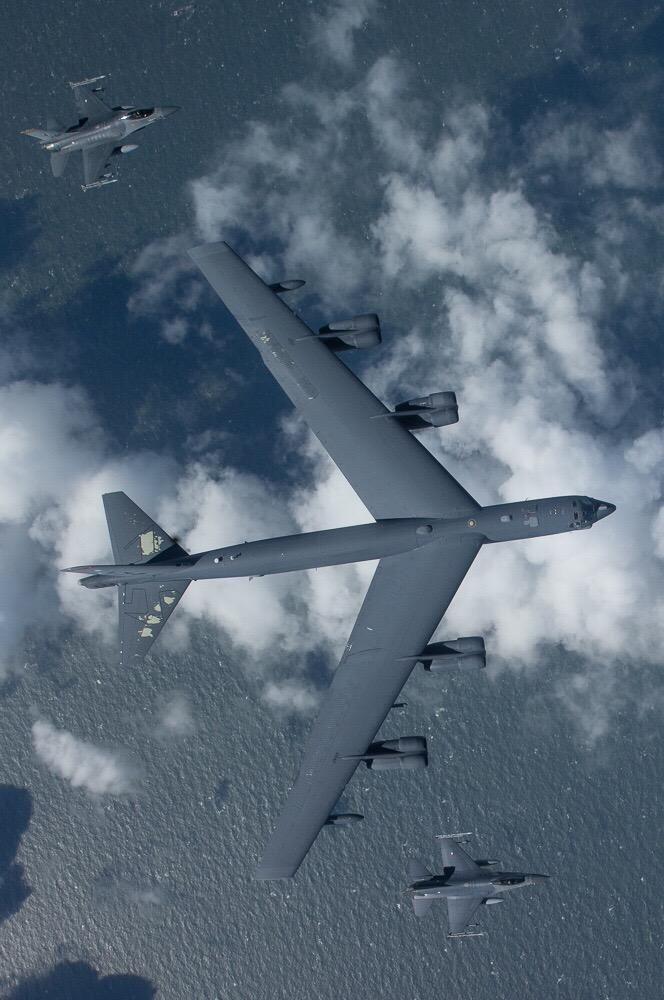 Bombardeiro americano B-52 escoltado por caças. Olha o tamanho da criança.