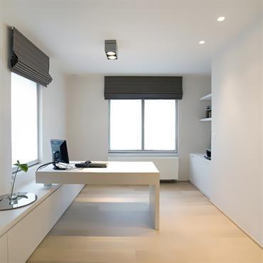 Bureau épuré avec murs et meubles blancs