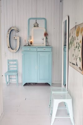 I love these white boarded walls and the white floor with colored furniture.