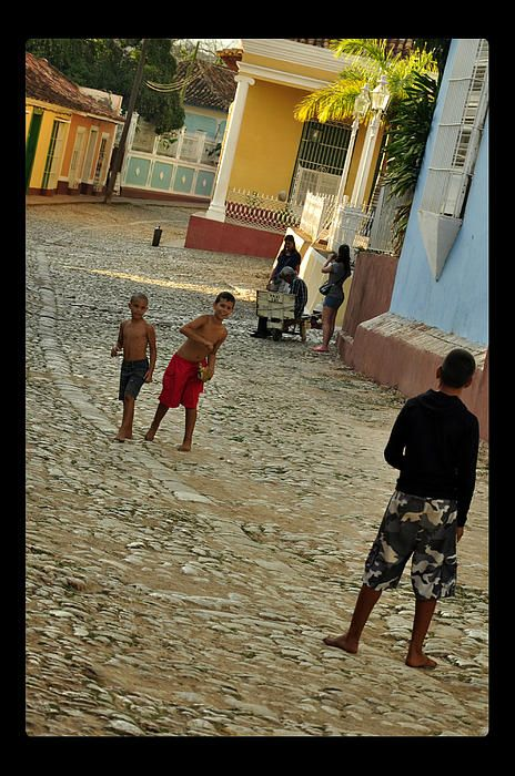 Boys playing baseball on the street in Trinidad UNESCO protected old town.