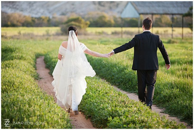 Wedding couple photo with couple walking down a jeep track in lush green grass - Photo taken at Kleinplasie Country House in Bredasdorp.  Photo by ZaraZoo Photography