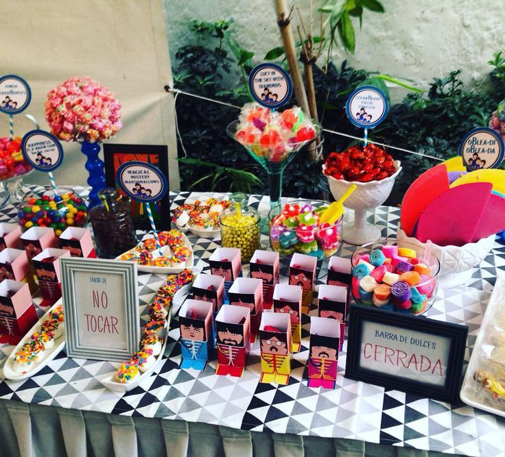 Beatles candy buffet table using specific beatles theamed candy like: twix & shout, ringo starrbursts, happiness is a warm gum (bang bang chew chew), magical mistery marshmallows, strawberry fields, yellow submarine cookies and candy bags that read: all you need is love .... And candy!