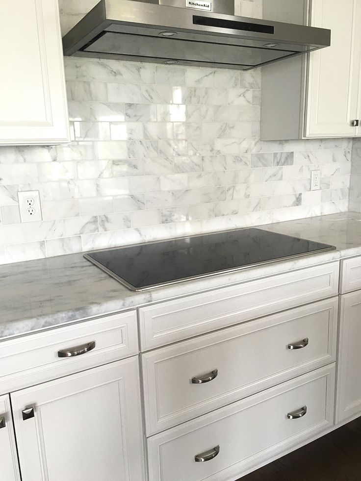 Carrera Marble Subway Tile Backsplash with white cabinets ...