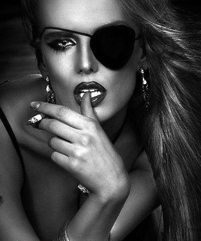 Фото Девушка с развивающимися волосами, дымящийся сигаретой в руках, с блестящими украшениями прикусывает палец