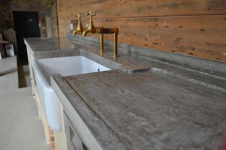 hand trowelled polished concrete worktop with sloped drainer and reclaimed bib taps