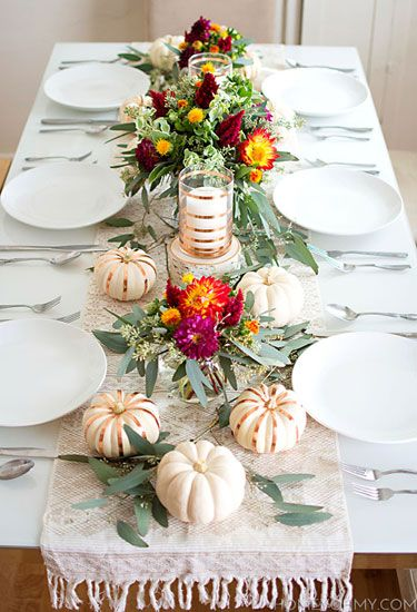 Stripes of copper tape adorn both the mini pumpkins and candle holders along thisThanksgiving table, while blooms from Trader Joe's provide bright pops of color.