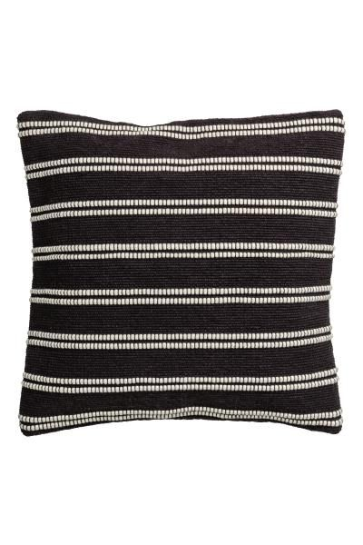Puuvillainen tyynynpäällinen, jossa jakardikudottu etupuoli. Yksivärinen kääntöpuoli kanvaasia. Piilovetoketju.
