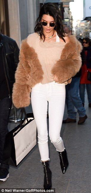 Effortless style: Keeping comfy but still cool, the Keeping Up With the Kardashians star paired the strides with a thin camel jumper, which she draped casually over one shoulder