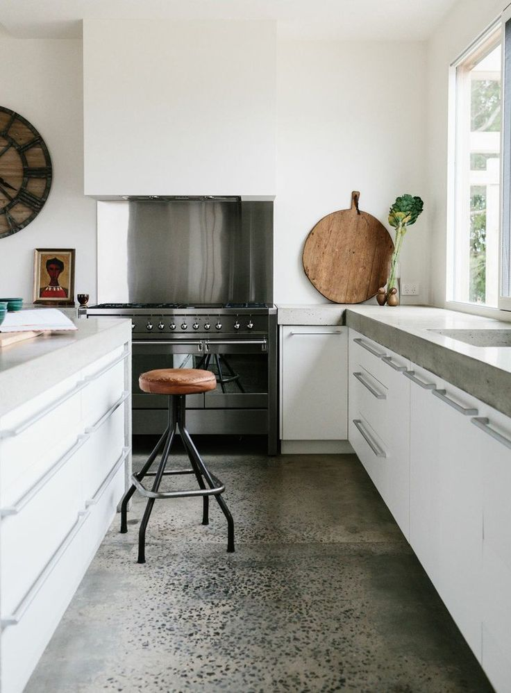 Trend Alert: Polished Concrete Floors via @MyDomaine...This minimal kitchen maximizes polished concrete impact on both floors and countertops, with white cabinets in between to keep the room feeling clean and bright. The leather stool adds a warm, well-worn touch to the room.
