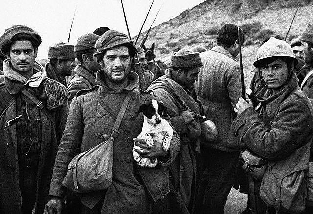 1937年頃。スペイン市民戦争、共和国派人民戦線兵士の取材写真。米国から義勇軍参戦したヘミングウェイの背中だけが写っている。1937, Spain --- A group of Republican soldiers talk to journalists during the Spanish Civil War, including the American novelist Ernest Hemingway (seen with his back to the camera), who served as a war correspondant.
