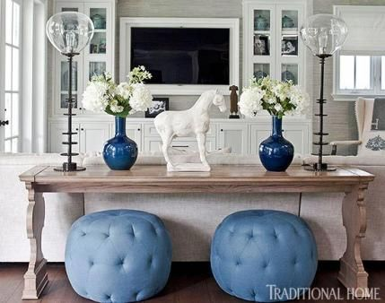Family Room in Blue and White  A pair of blue linen poufs are tucked beneath a sofa table from Hickory Chair in the family room, decorated i...