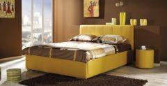 Łóżko Afrodyta a+b o tapicerowane w żółtej eko skórę, obok stoliczek nocny Afrodyta żółty.