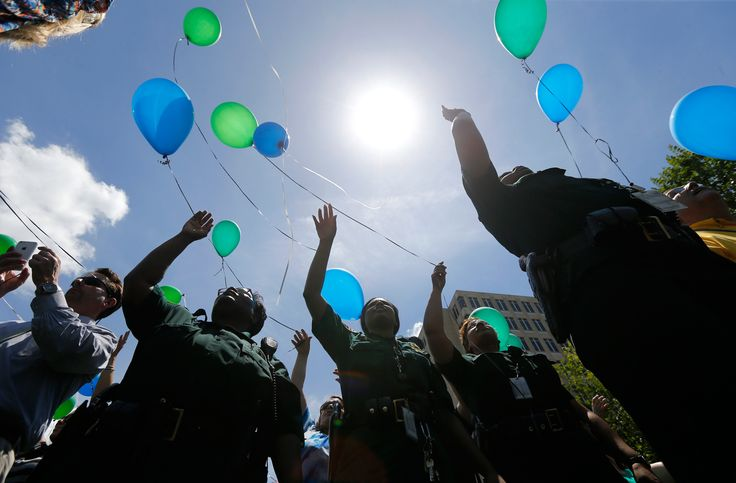 East Baton Rouge Sheriff's deputies release balloons at a noon vigil organized by municipal court workers in downtown Baton Rouge, Louisiana, Wednesday, July 20, 2106. The vigil was held in honor of the recent slain and injured sheriff deputies and police officers who were killed and wounded in a shooting near a gas station in Baton Rouge on Sunday morning, less than two weeks after a black man was shot and killed by police, sparking nightly protests across the city.