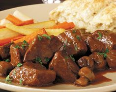 Beef tips in wine sa2 medium onions, sliced  1/2 stick butter  1/4 cup vegetable oil  2 1/2 pounds beef filet, 1-inch cubed  1/2 cup flour  1 -10.5 oz beef bouillon  1 cup dry red wine  1/2 pound fresh mushrooms, sliced  Salt & pepper to taste  Dried thyme, oregano, basil and fresh parsley