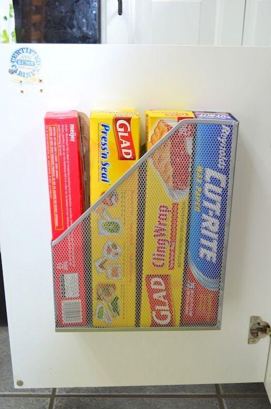 Acessório para organizar papéis e documentos foi fixado no armário para colocar rolos de papel filme, papel manteiga e papel alumínio.