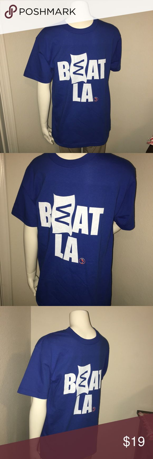 """MLB cubs SS """"BEAT LA"""" W flag shirt sz: M Thank you for viewing my listing, for sale is a men's, Chicago cubs, short sleeve graphic T-shirt. The T-shirt says """"BEAT LA"""" with the """"E"""" in beat being the cubs """"W"""" flag.  Very awesome shirt. The shirt is in excellent condition like new!  No rips or stains, if you have any questions or would like additional photos please feel free to ask.  From under one arm to under the other measures appx 20"""" from the top of the shoulder to the bottom of the shirt…"""