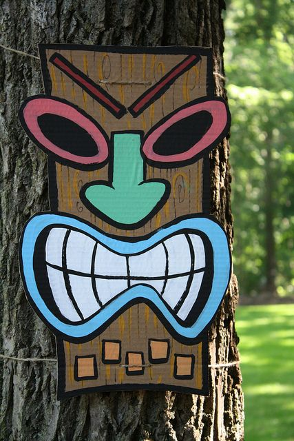 Luau party with DIY style...  fun cardboard posters, tiki masks, flowers, and umbrella wreath