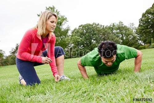 Trainer coaching man doing push ups