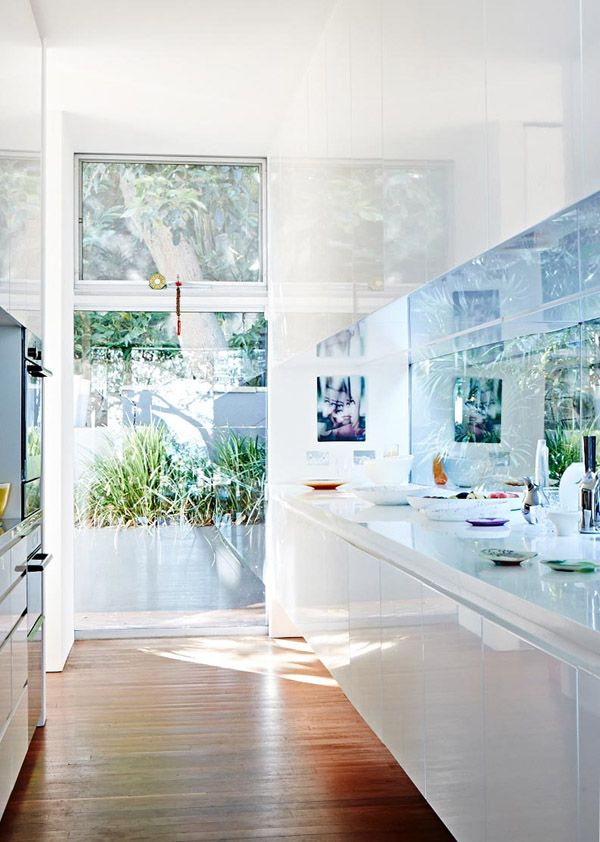 while I am not an all-modern girl this austere shiny white kitchen with its amazing glass wall and glass backsplash are fantastic