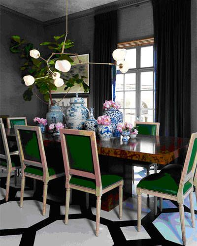 """The green leather dining chair and bold patterned painted floor pop against the walls."""