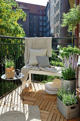Ławka na balkonie. Prosta skandynawska ławka dzięki pledowi i poduszkom stała się wygodnym miejscem do wypoczynku na tym balkonie. Uroczym elementem wyposażenia jest ministolik z blatem-tacą. Uwagę zwraca piękna podłoga z drewnianych podestów tworzących efektowną mozaikę.