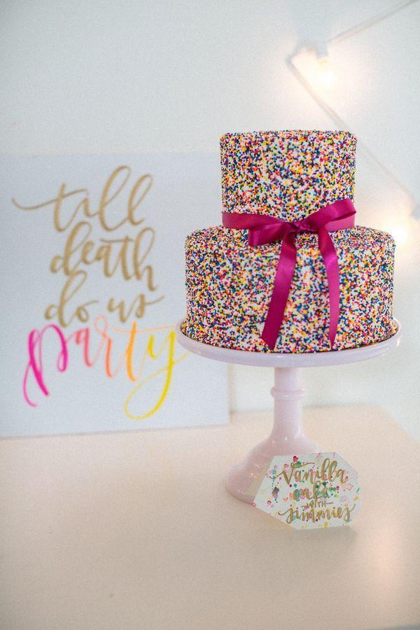 Playful wedding cake covered in rainbow sprinkles | Photo by Stevi Sayler