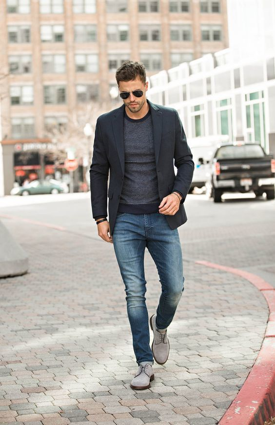 Shop this look on Lookastic: https://lookastic.com/men/looks/blazer-crew-neck-sweater-jeans/18759 — Black Blazer — Charcoal Crew-neck Sweater — Blue Jeans — Grey Suede Derby Shoes — Black Sunglasses