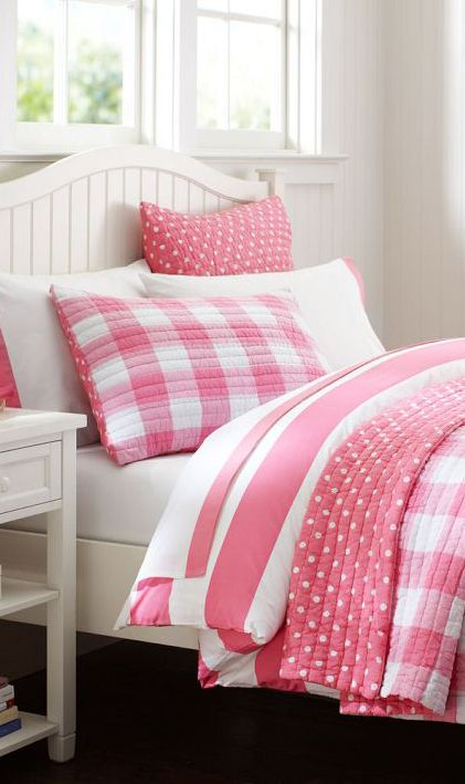 Pink & white plaid and polka dot bedding against white bedroom furniture