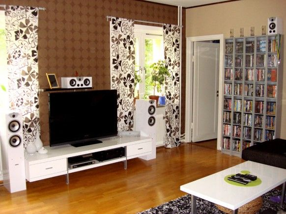 Living Room:Living Room Setups: Arrange Your Entertainment Room Amazing Living Room Tv Setup Idea With Flowery Curtain And Brown Wallpaper Wall Shelving To Store Book And CD Collection White Coffee Table Hardwood Floor