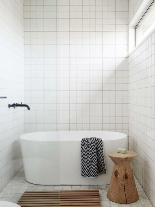 Stacked square wall tile in white with square marble floor tile. Simple.