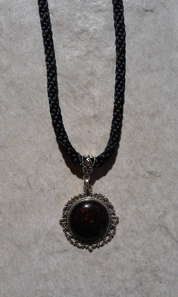 The medal on the kumihimo necklace is a black-gleaming red cabochon.