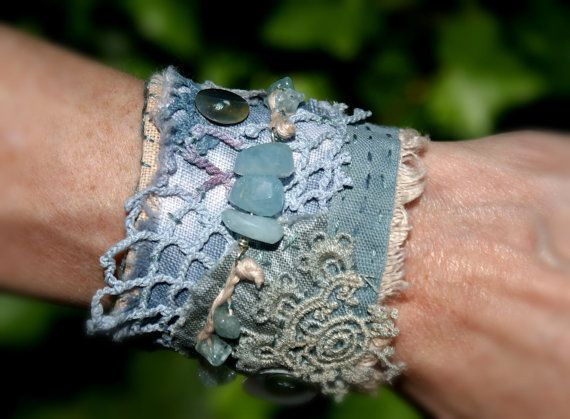 I made this bohemian textile cuff bracelet with layers of linen fabric, vintage lace and crochet.  Its adorned with gorgeous blue Aquamarine beads, the three in the centre are quite chunky and are thread on sterling silver wire. The aquamarine chip beads are braided together with linen twine. For some extra beauty i have sewn some shell buttons onto the bracelet.  The colours are moody blue, beige and ivory.  On the lining fabric there is the quote: when i want to see LOVE defined i look at…