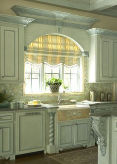 Arched windows over sink with roman shade and molding connecting to cabinets. The cornices and roman shade really complete the look!
