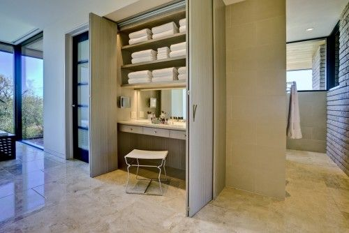 The contemporary make-up vanity in this John Senhauser Architects bathroom design is hidden inside a wardrobe-style closet, staying with the sleek look of the room by keeping clutter out of the way when it's not in use.